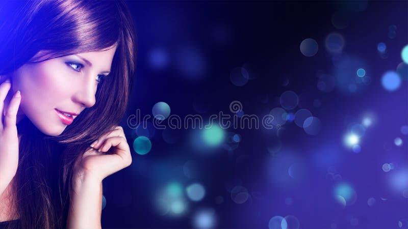 Aantrekkelijke donkerbruine vrouw met bokehachtergrond stock foto