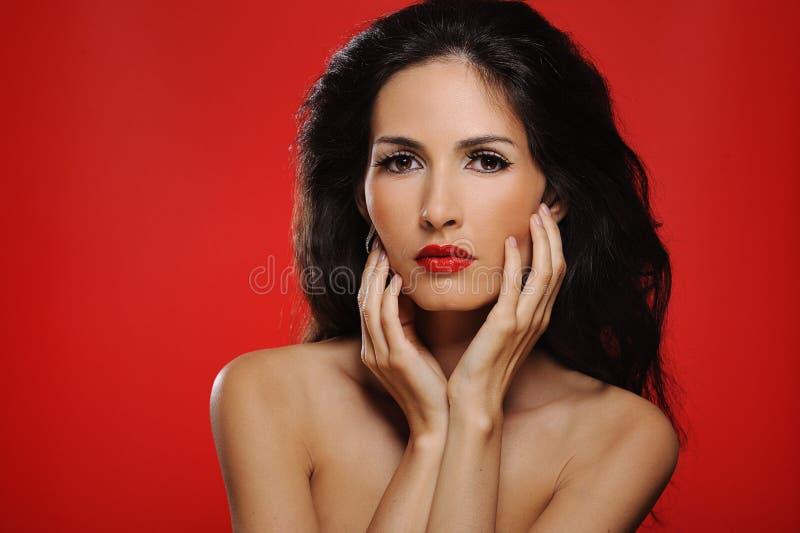 Aantrekkelijke donkerbruine vrouw met prachtig haar wat betreft haar gezicht royalty-vrije stock afbeeldingen