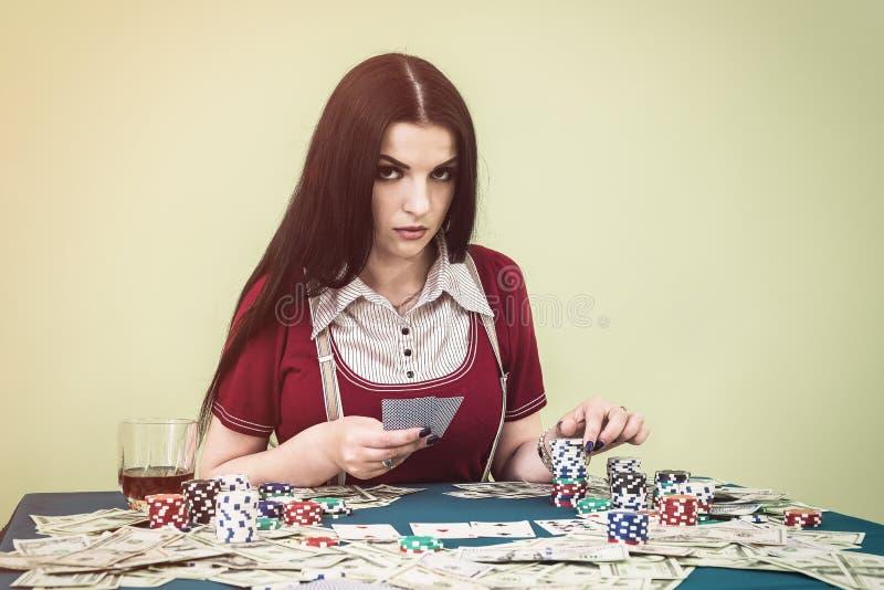 Aantrekkelijke donkerbruine vrouw met speelkaarten en pooklijst stock fotografie