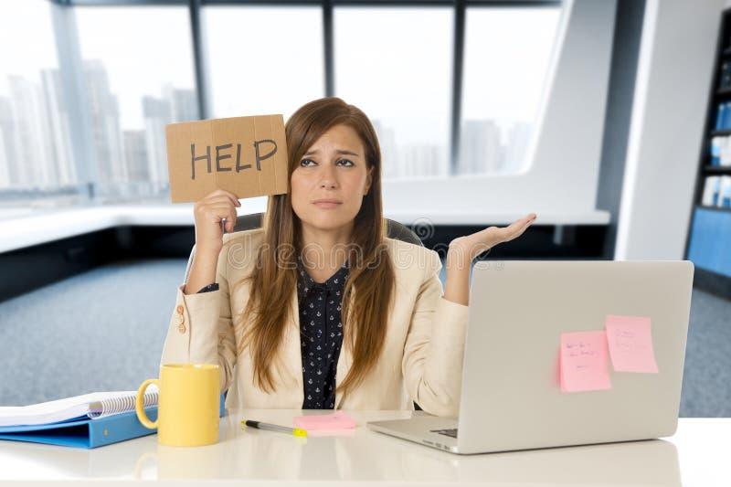 Aantrekkelijke droevige en wanhopige bedrijfsvrouw die aan spanning lijden bij bureaulaptop het teken van de de holdingshulp van  royalty-vrije stock foto