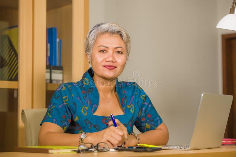 Aantrekkelijke en gelukkige succesvolle midden oude Aziatische vrouw die bij laptop computerbureau werken die zekere dragende ele royalty-vrije stock afbeeldingen