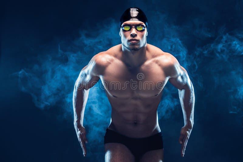Aantrekkelijke en spierzwemmer Studio van jonge shirtless sportman op zwarte achtergrond wordt geschoten die Mensen met glazen stock fotografie