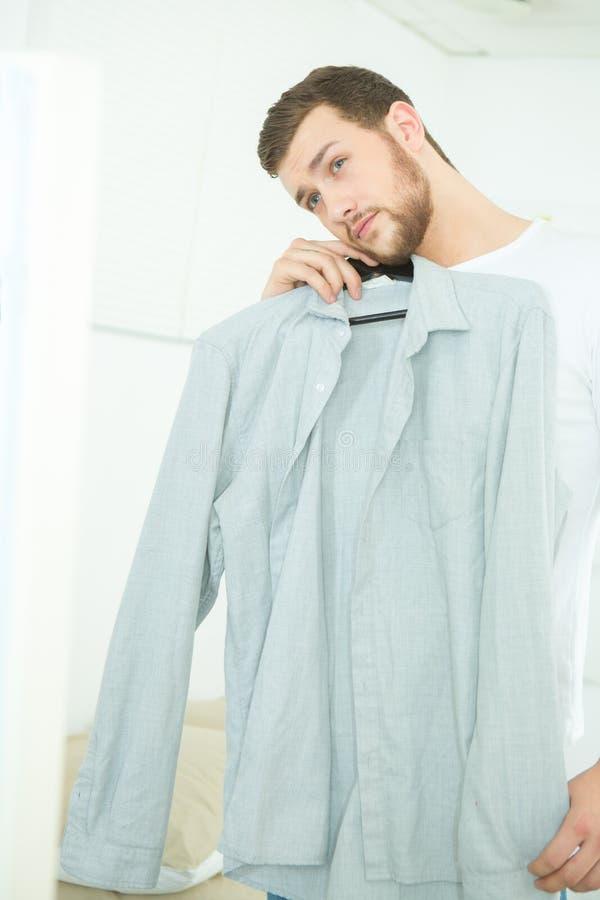 Aantrekkelijke en sterke jonge mens die overhemd kiezen royalty-vrije stock afbeeldingen