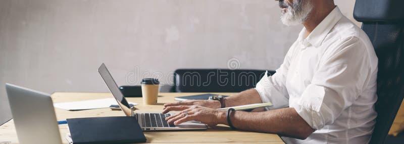 Aantrekkelijke en vertrouwelijke volwassen zakenman die mobiele laptop computer met behulp van terwijl het werken bij de houten l royalty-vrije stock afbeelding