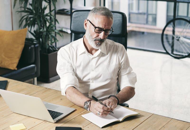Aantrekkelijke en vertrouwelijke volwassen zakenman die mobiele laptop computer met behulp van terwijl het werken bij de houten l stock foto's