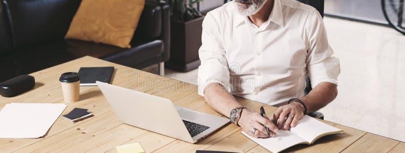 Aantrekkelijke en vertrouwelijke volwassen zakenman gebruikend mobiele laptop computer en makend nota's terwijl het werken bij ho royalty-vrije stock foto's