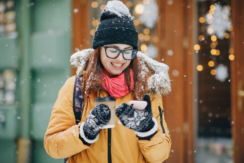 Aantrekkelijke en vrolijke jonge vrouw die smartphone in een straat gebruiken Zij controleert post, praatjes of het nieuws Stad b stock foto