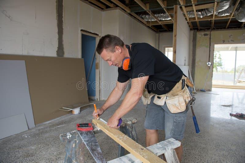 Aantrekkelijke en zekere aannemerstimmerman of bouwersmens die metend hout met handzaag bij industrieel bouwsi werken royalty-vrije stock fotografie
