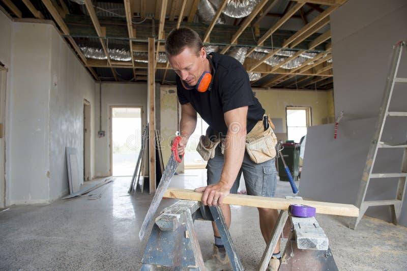 Aantrekkelijke en zekere aannemerstimmerman of bouwersmens die scherp hout met handzaag in industriële bouwbaan werken royalty-vrije stock fotografie