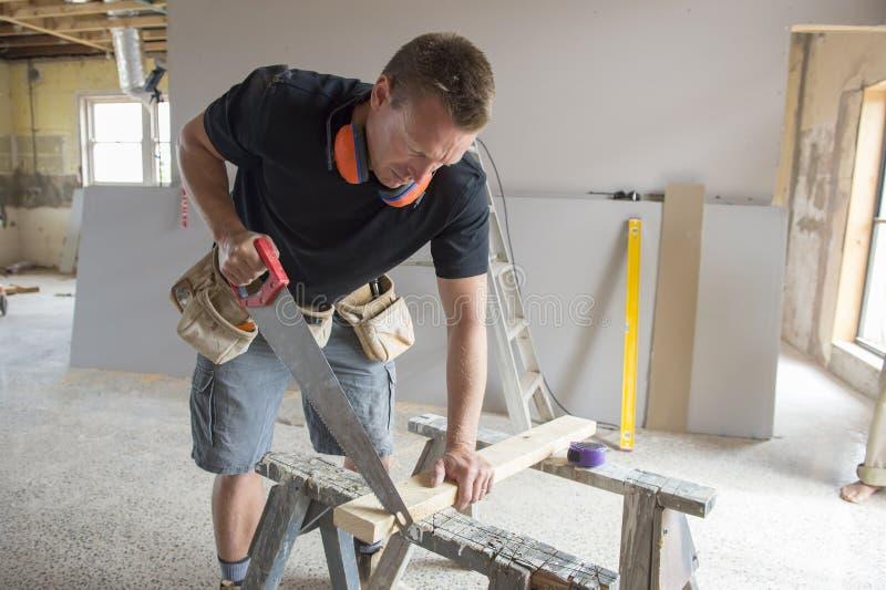 Aantrekkelijke en zekere aannemerstimmerman of bouwersmens die scherp hout met handzaag in industriële bouwbaan werken stock foto's