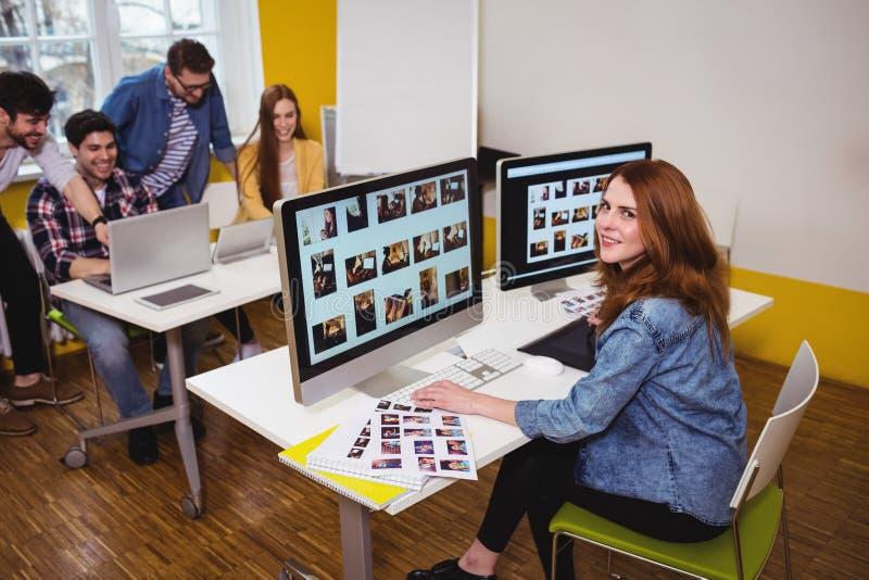 Aantrekkelijke fotoredacteur die aan computers werken royalty-vrije stock foto