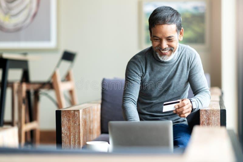 Aantrekkelijke gebaarde hipster Aziatische vader of Spaanse oude mens die Laptop en creditcardbetaling gebruiken die online met k stock fotografie