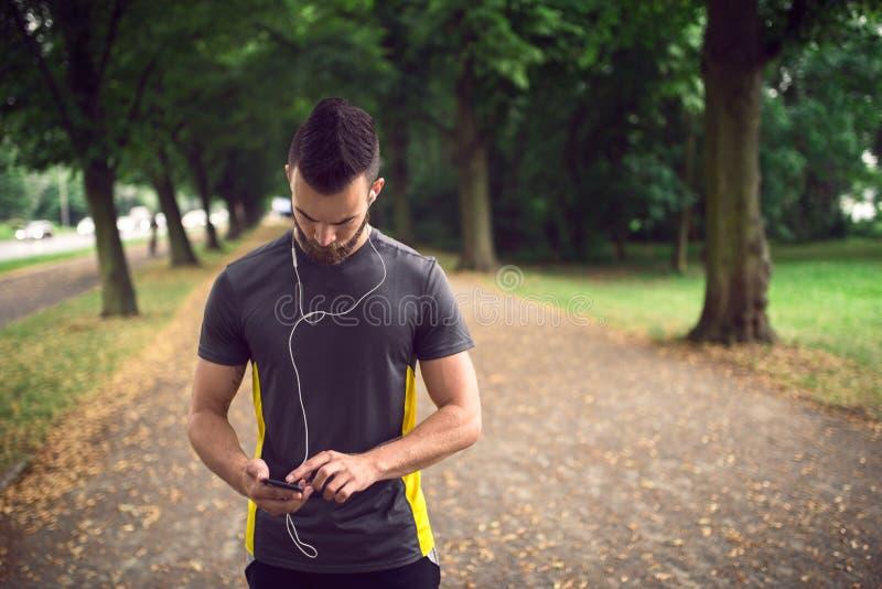 Aantrekkelijke gebaarde mens die aan muziek luisteren stock foto