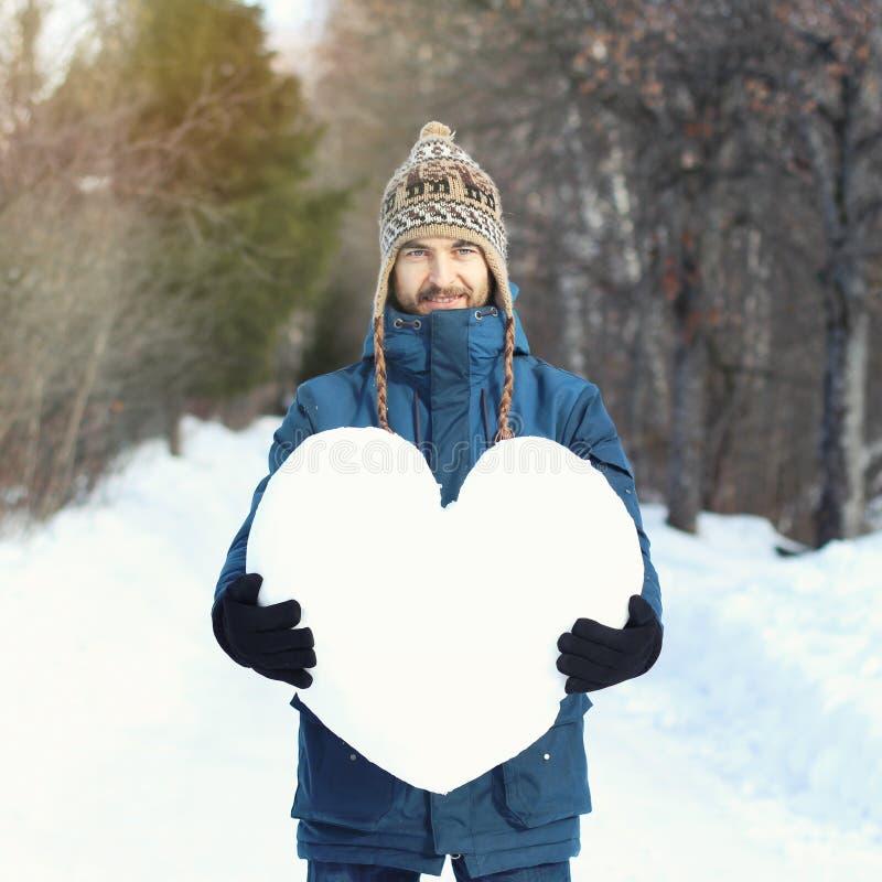 Aantrekkelijke gebaarde mens die een reusachtig die hart houden van sneeuw wordt gemaakt, die zich op sneeuwweg in de winterpark  stock foto's
