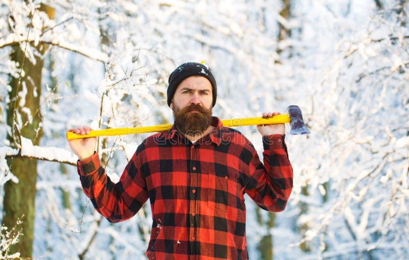 Aantrekkelijke gebaarde mens in openlucht in de winter Een mens in een de winter bosa houthakker die in het bosmens inspecteren w royalty-vrije stock fotografie