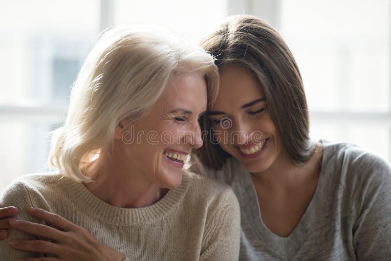 Aantrekkelijke gegroeide dochter en het midden oude moeder lachen royalty-vrije stock afbeelding