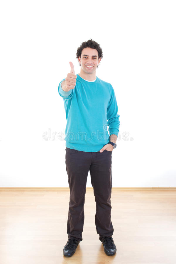 Aantrekkelijke gelukkige jonge mens die tonend duim bevinden zich stock foto