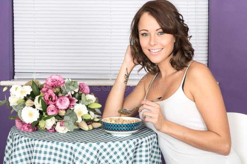 Aantrekkelijke Gelukkige Jonge Vrouw die Ontbijtgraangewas eten stock foto