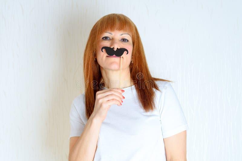 Aantrekkelijke gelukkige midden oude vrouw die pret met een valse snor op stok heeft stock foto's