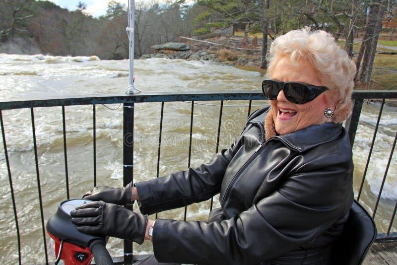 Aantrekkelijke, gelukkige oudste op haar rode autoped royalty-vrije stock foto's