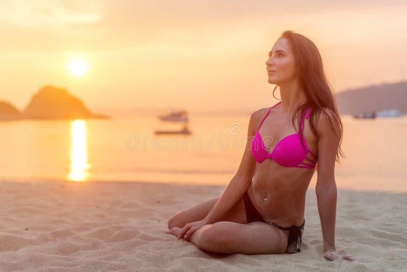 Aantrekkelijke geschikte jonge donkerbruine vrouw die bikinizitting op overzees strand dragen bij zonsondergang royalty-vrije stock foto