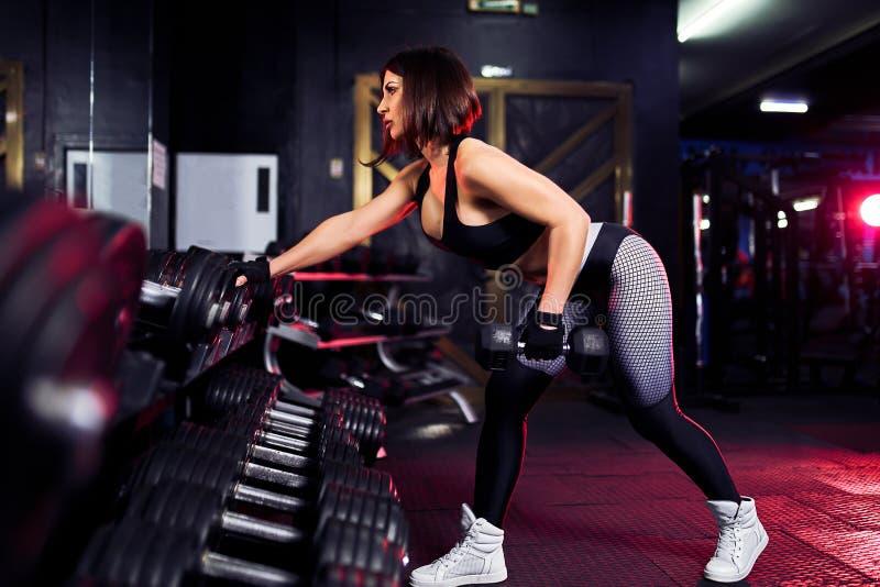Aantrekkelijke geschikte middenleeftijdsvrouw in de gymnastiek crouches met een barbell Vrouw die terug opleiden stock afbeelding
