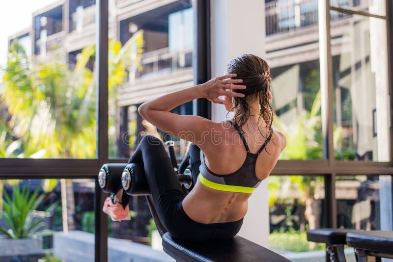 Aantrekkelijke geschikte vrouw die abs in geschiktheidsgymnastiek uitwerken bij het hotel van de luxetoevlucht met een grote meni royalty-vrije stock afbeeldingen