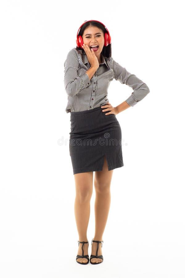 Aantrekkelijke glimlachende Aziatische jonge dame die rode hoofdtelefoons dragen die zich met blije die gebaren bevinden op witte stock foto's