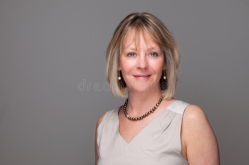 Aantrekkelijke Glimlachende Elegante Vrouw op Grijs royalty-vrije stock fotografie