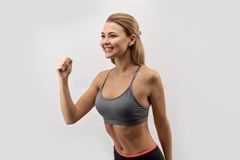 Aantrekkelijke glimlachende jonge vrouw met een geschikt atletisch lichaam in sport royalty-vrije stock fotografie