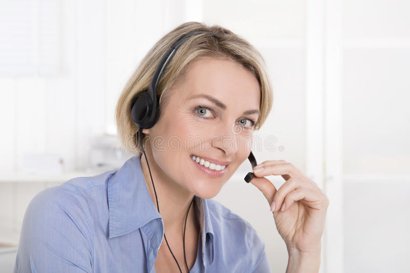 Aantrekkelijke glimlachende midden oude vrouw in blauw die met headse roepen stock fotografie