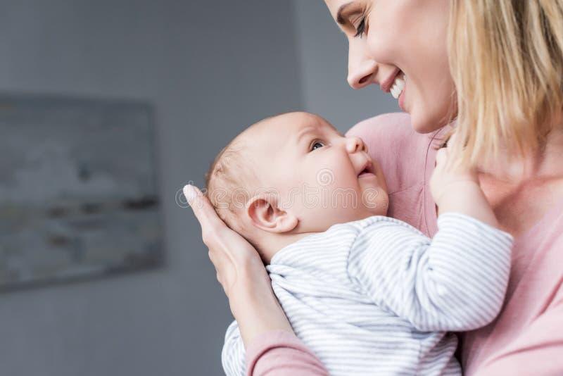 aantrekkelijke glimlachende moeder die haar pasgeboren houden stock afbeelding