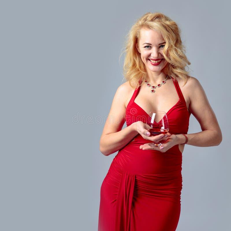 Aantrekkelijke glimlachende rijpe vrouw in rode avondjurk met cognacglas brandewijn royalty-vrije stock afbeelding