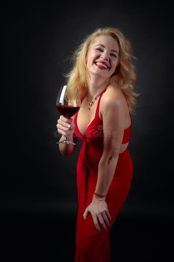 Aantrekkelijke glimlachende rijpe vrouw in rode avondjurk met glas rode wijn stock afbeeldingen