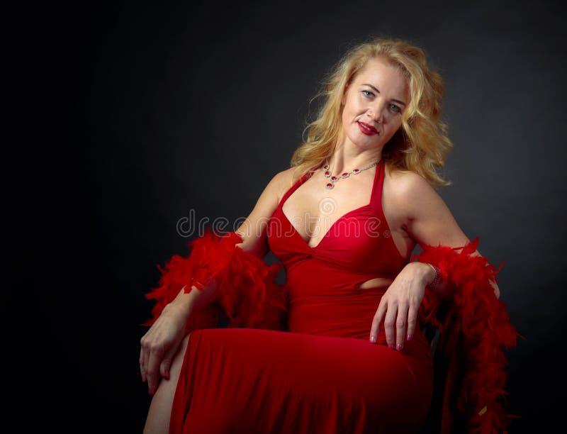 Aantrekkelijke glimlachende rijpe vrouw in rode avondjurk met pluizige veerboa stock afbeelding