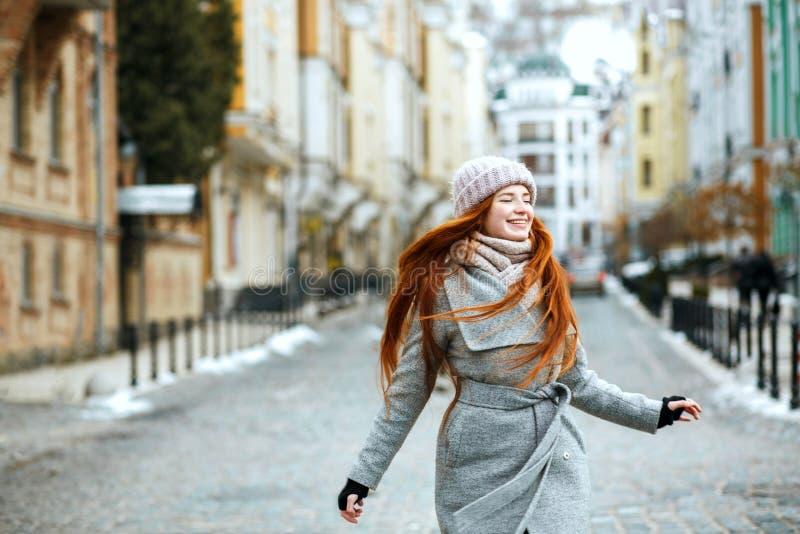 Aantrekkelijke glimlachende rode haired vrouw die modieuze de winteroutfi dragen stock afbeeldingen