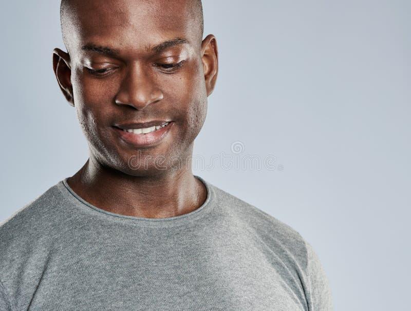 Aantrekkelijke grijnzende mens die benedenwaarts kijkt stock fotografie