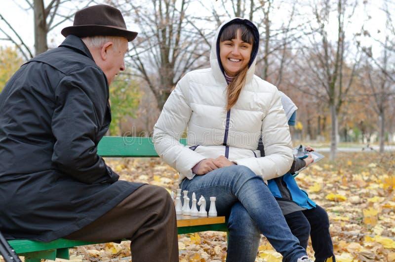 Aantrekkelijke het glimlachen vrouwenzitting op een parkbank het spelen schaak met een bejaarde royalty-vrije stock foto's