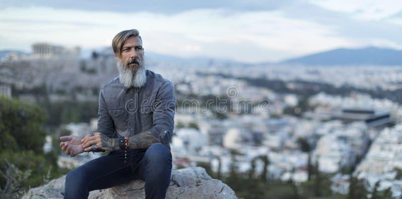 Aantrekkelijke hipster met een baard zit op een rots hoog over de Stad van Athene met Akropolismening stock foto