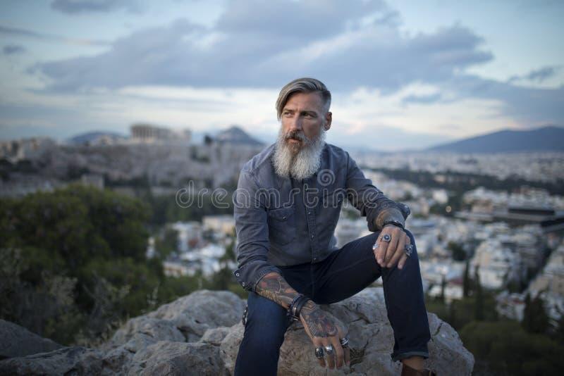 Aantrekkelijke hipster met een baard zit op een rots hoog over de Stad van Athene met Akropolismening bij zonsondergang royalty-vrije stock foto's