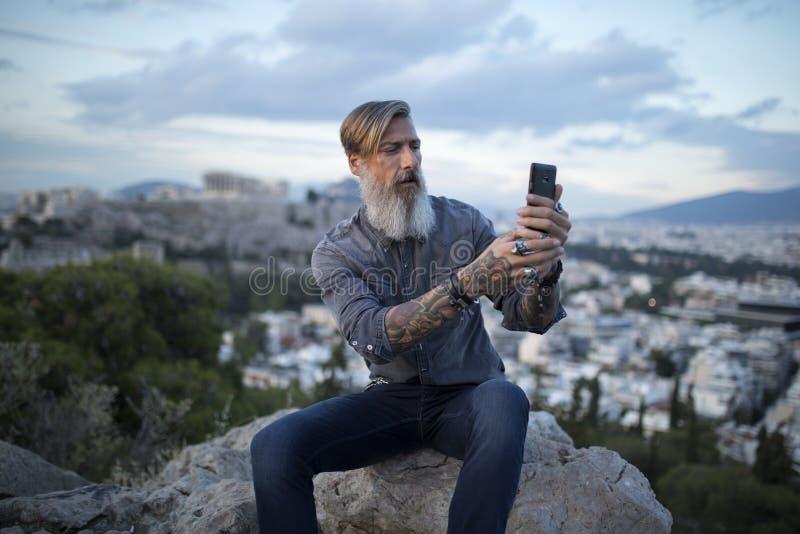 Aantrekkelijke hipster met een baard zit op een rots hoog over de Stad van Athene met Akropolismening en maakt een selfie royalty-vrije stock afbeeldingen