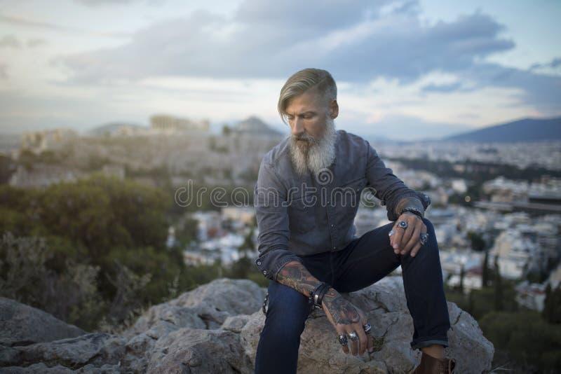 Aantrekkelijke hipster met een grijze baard zit op een rots hoog over de Stad van Athene met Akropolismening royalty-vrije stock afbeelding