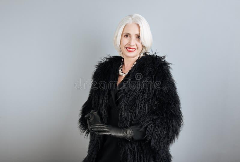 Aantrekkelijke hogere vrouw die zich tegen geïsoleerde achtergrond bevinden stock afbeeldingen