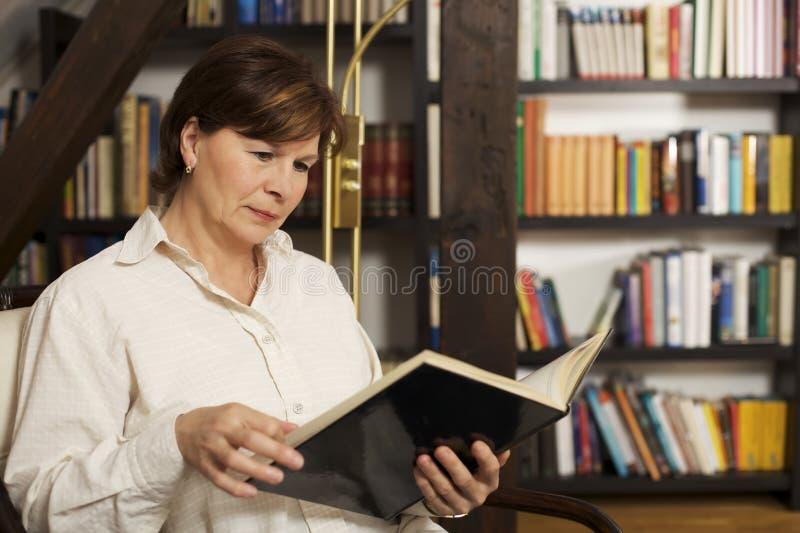 Aantrekkelijke hogere vrouwenzitting en lezing een boek royalty-vrije stock foto