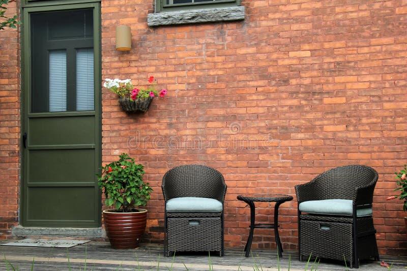 Aantrekkelijke houten portiek met openluchtmeubilair van oud baksteenhuis. stock fotografie
