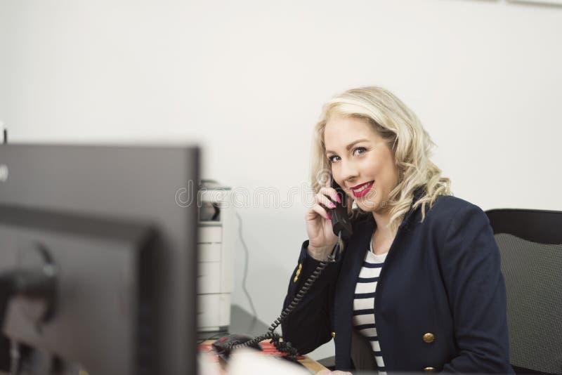 Aantrekkelijke jaren '30vrouw die op kantoor met telefoon werken royalty-vrije stock afbeeldingen
