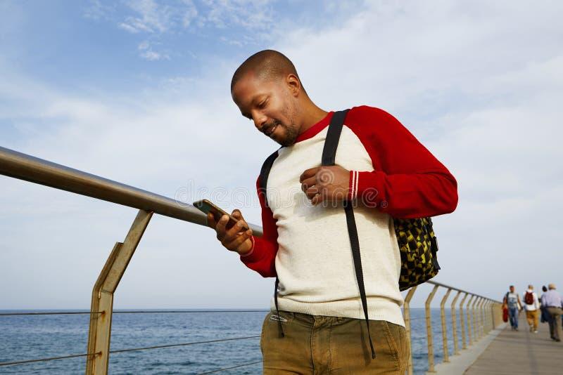 Aantrekkelijke jonge Afrikaans-Amerikaanse reizigersmens die mobiele telefoonhand in openlucht van stad gebruiken Bewolkte hemel  stock afbeeldingen