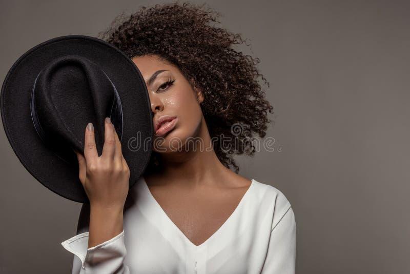 Aantrekkelijke jonge Afrikaanse Amerikaanse vrouw die in wit overhemd zwarte hoed meer dan de helft van haar gezicht houden stock foto