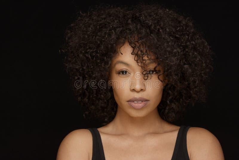 Aantrekkelijke jonge Afrikaanse Amerikaanse vrouw met krullend natuurlijk haar royalty-vrije stock fotografie