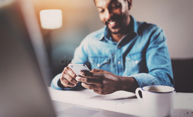 Aantrekkelijke jonge Afrikaanse mens die smartphone gebruiken terwijl het zitten van bij de houten lijst zijn modern huis Concept stock foto